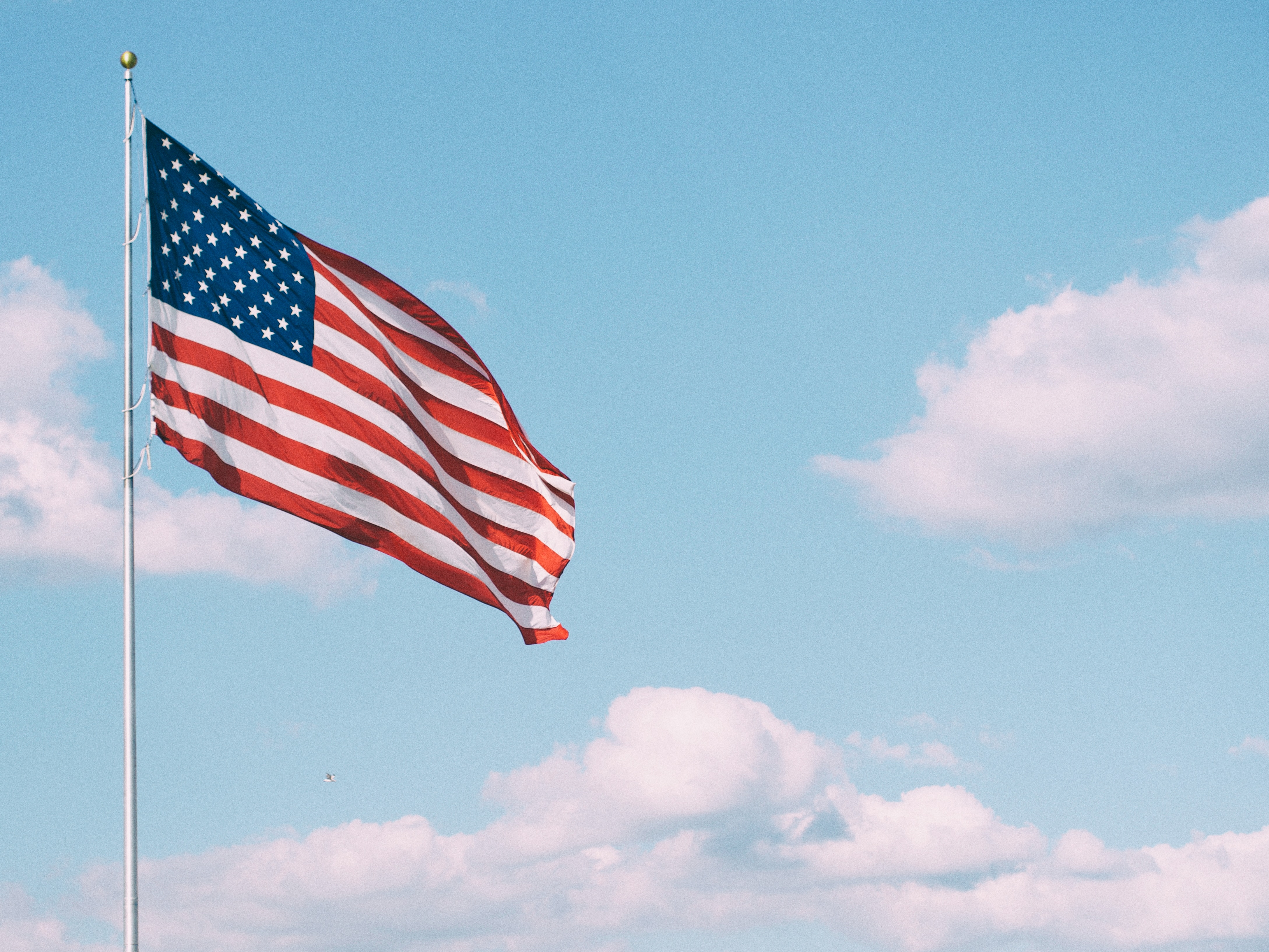 American Flag with a blue sky in the background.