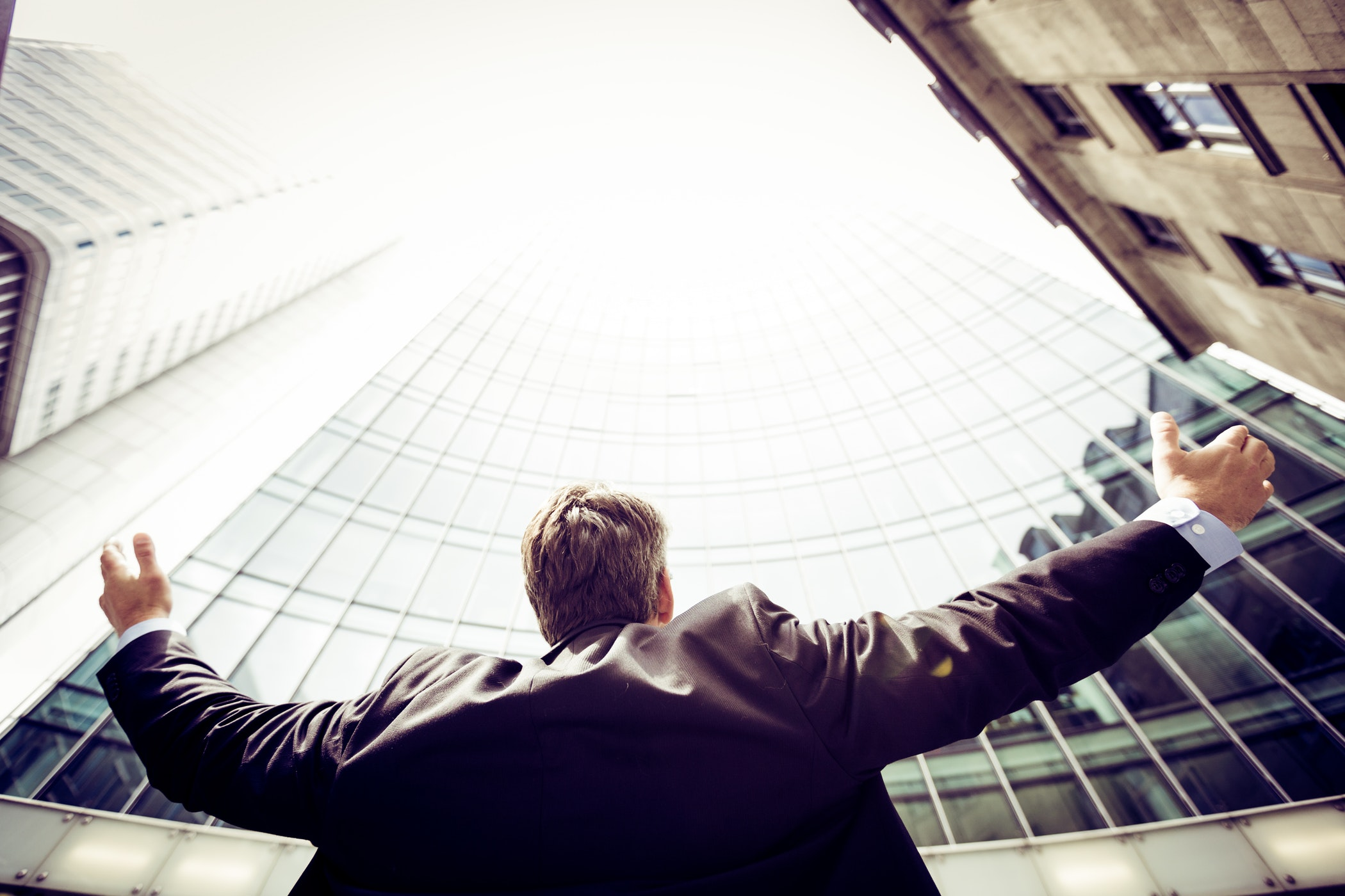 Business man with arms stretched out in success, looking up at tall buildings