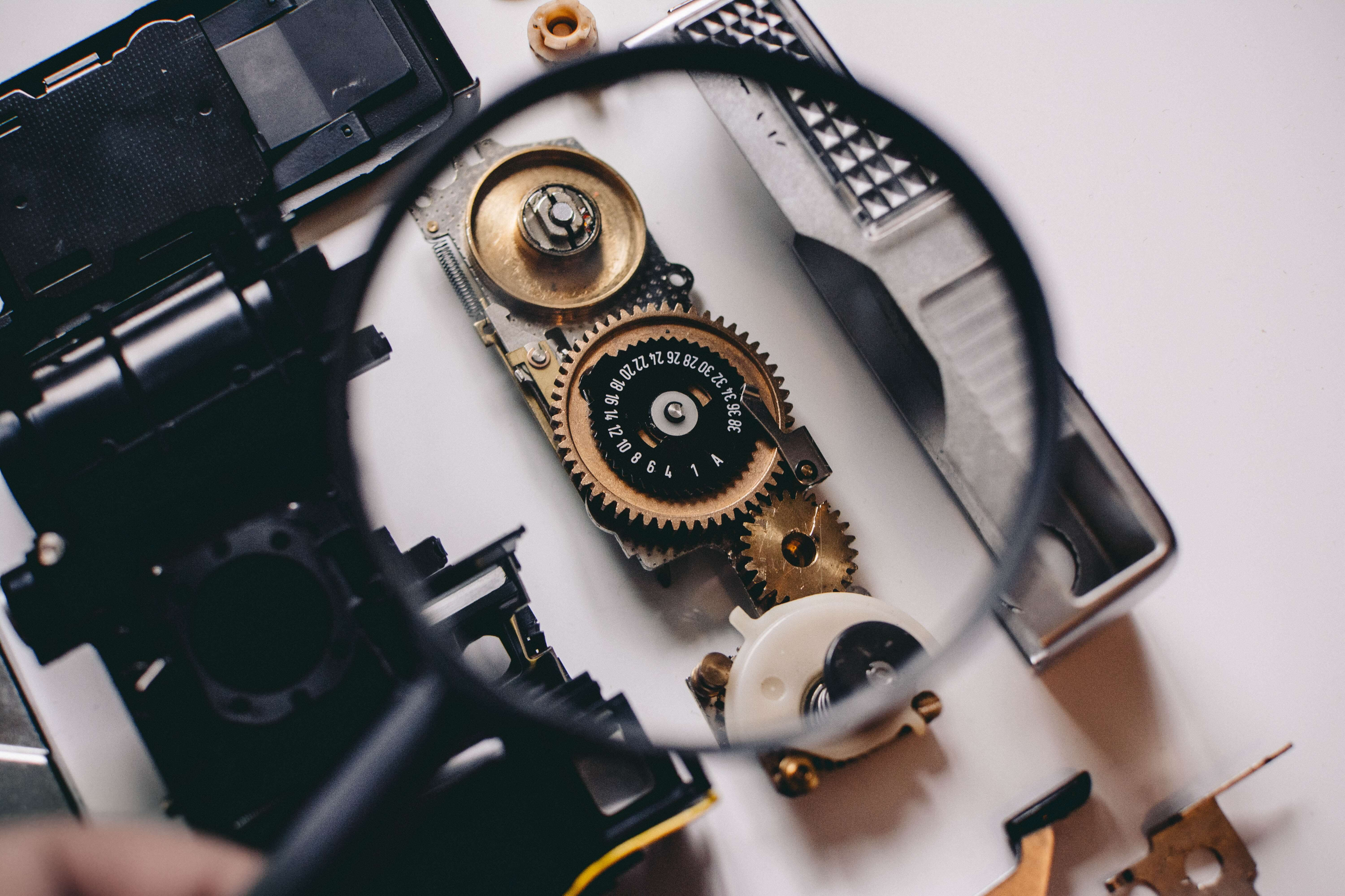 Magnifying glass inspecting the gears of a device