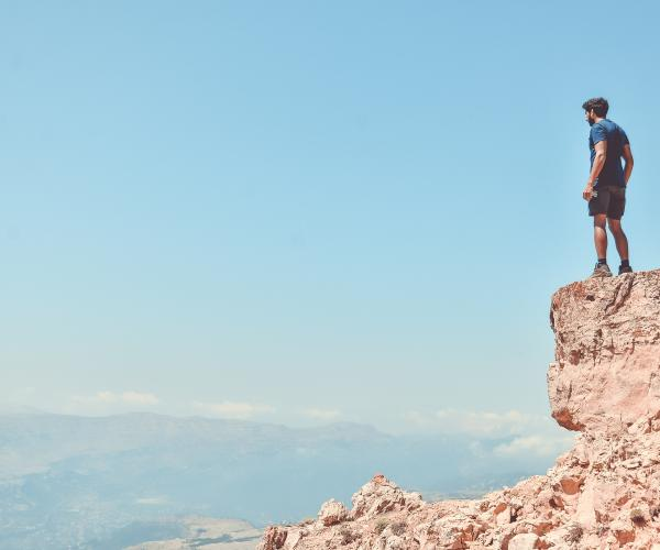 Man standing on top of a rock looking out over a landscape