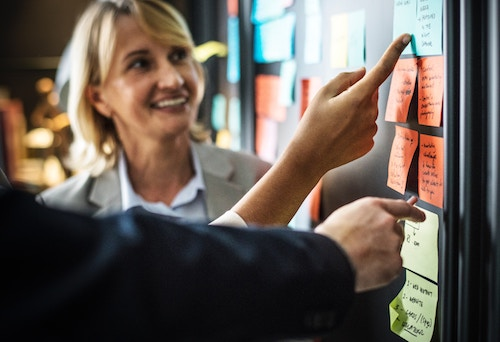 Woman working with a certified scrum master at a board.